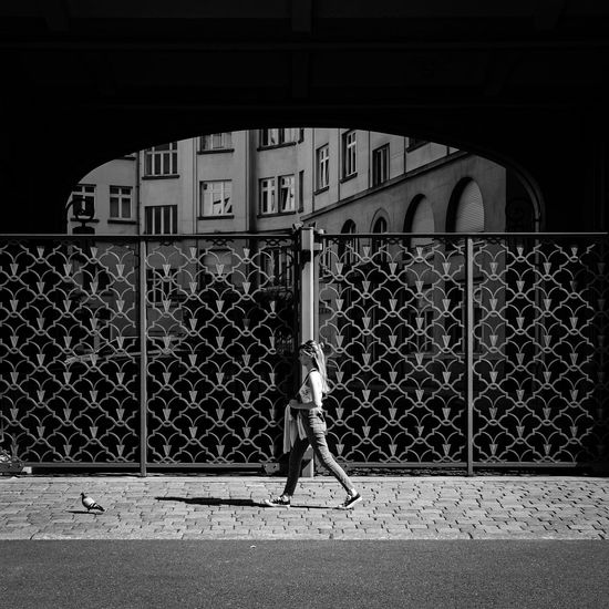 Piétons ... Urban Perspectives Street Photography Black & White Monochrome Black And White Walking Around The Devil's In The Detail Street Sidewalk Architectural Detail Real People Bird Woman Architecture Built Structure Building Exterior Security Gate Protection Building Metal Fence Safety Barrier Day Boundary City Closed Full Length Entrance Arch The Street Photographer - 2019 EyeEm Awards