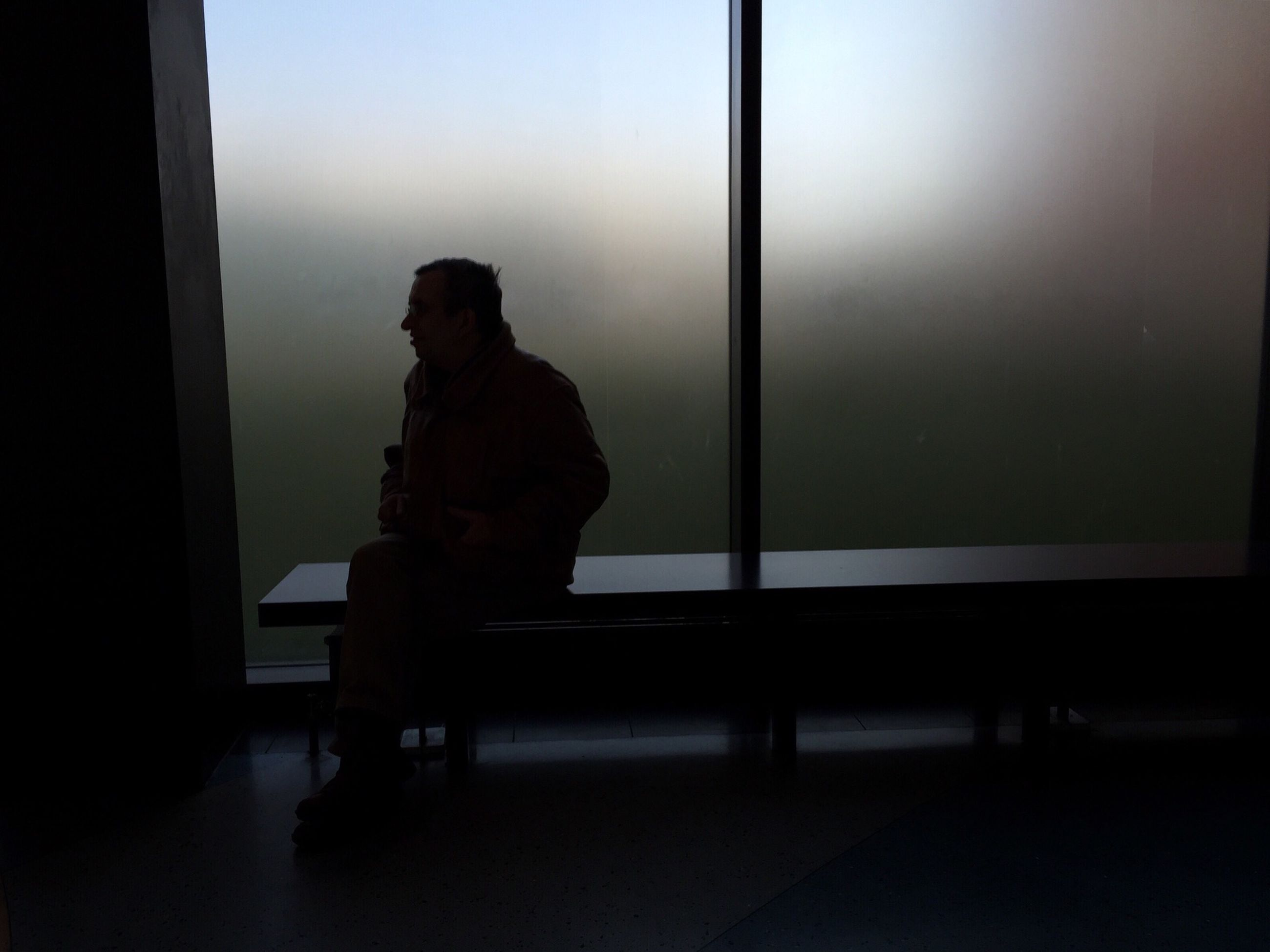 indoors, window, glass - material, home interior, transparent, silhouette, sitting, lifestyles, looking through window, leisure activity, standing, three quarter length, human representation, contemplation, young adult, built structure, side view, full length