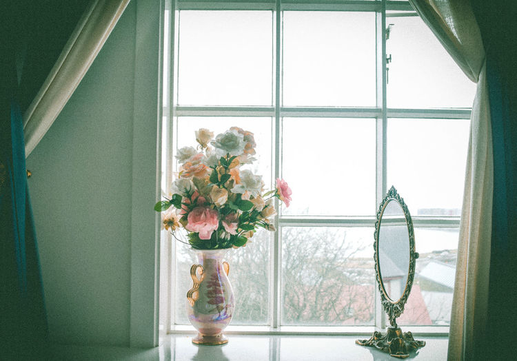 Close-up of flower vase on window sill