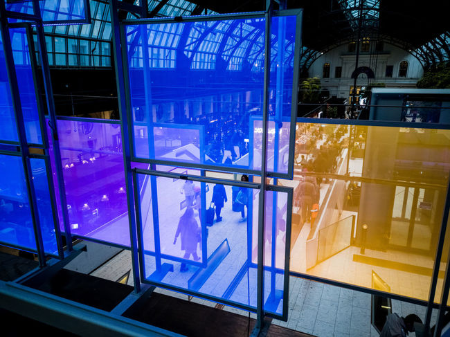 Purple Yellow Orange Blue Combination Glass - Material Commute Decor Top Floor Ceiling Travel Station Spacious Modern Converted Building Illuminated Window Architecture Built Structure Entryway Entrance Pixelated