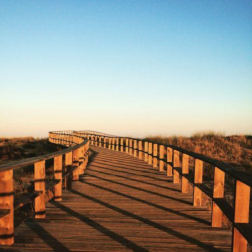 Footbridge over field against clear sky