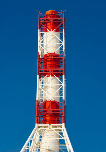 Low angle view of red tower against clear blue sky