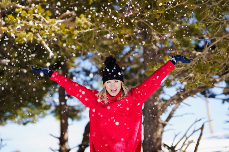 Close-up of person on snow covered tree during winter