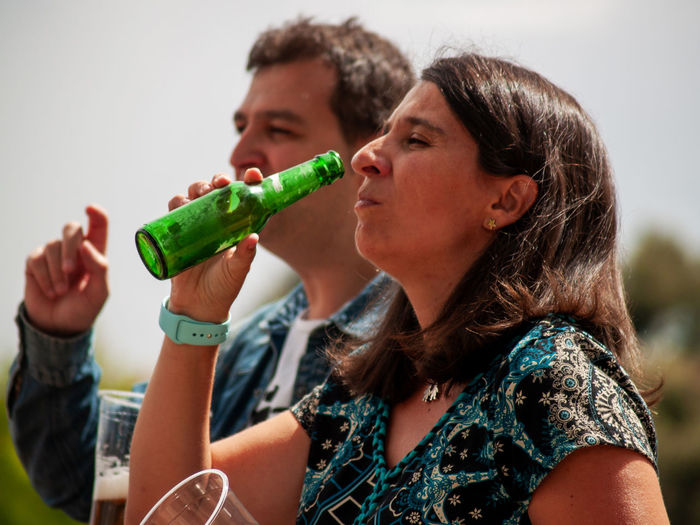 Man and woman drinking beer against sky
