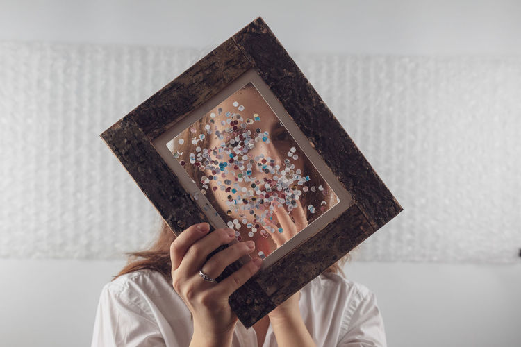 Portrait of woman covering face with picture frame at home