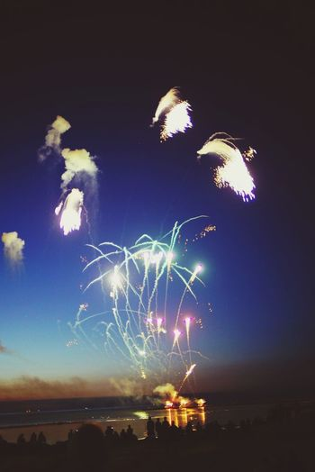 Night Firework Display Celebration Event Arts Culture And Entertainment Exploding Firework - Man Made Object Long Exposure Sky Motion Blurred Motion Outdoors Multi Colored Beach Sea Nature