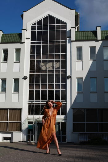 Glamorous urban photography, chic image of model in golden silk dress outdoors posing near building