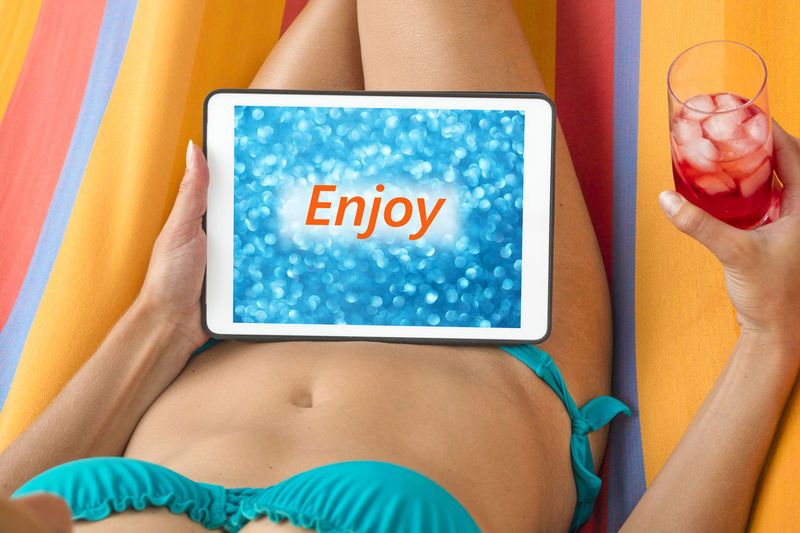 Midsection Of Young Woman Wearing Bikini Using Digital Tablet While Resting On Towel Outdoors