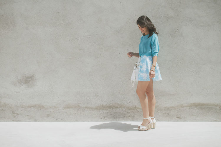 Fashion photo of a beautiful elegant young woman with a pretty palm print mini skirt and blue shirt holding handbag posing over cement background. Full Length One Person Women Lifestyles Leisure Activity Casual Clothing Wall - Building Feature Day Real People Standing Architecture