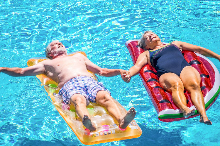 Old people senior couple relax and sleep on the blue swimming pool clear water lay down on trendy coloured inflatabler mattress lilos and taking hands with love for forever together lifestyle concept Active Activity Adult Aged Air Background Blue Caucasian Cheerful Colors Coloured Couple Elderly Enjoy Enjoying Floating Friends Fun Happiness Holiday Home Hotel Inflatable  Leisure Lilo Mattress Mature Old Outdoor People Playful Pool Recreation  Relaxed Residence Resort Retired Senior Summer Sun Sunbath Swimming Swimming Pool Trendy Tropical Vacation Village Water Watermelon White