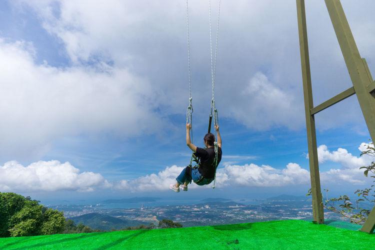 Rear view of woman swinging on swing against sky