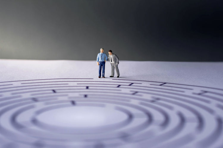 Challenge and Success Concept. present by two Miniature Figure of Businessman standing on the Maze Paper. one of them act like a Coach or Boss Maze Teamwork Beginnings Boss Complexity Consulting Contemplation Couple - Relationship Full Length Indoors  Males  Management Mature Adult Mature Men Men Mid Adult Mid Adult Men People Planning Rear View Solution Standing Strategy Success Two People