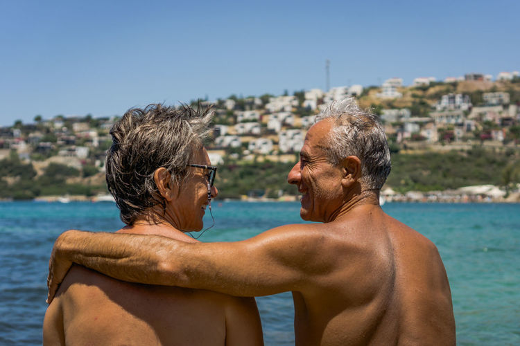 Rear view of shirtless couple standing at beach against clear sky