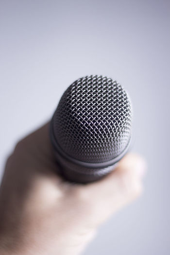 Close-up of hand holding microphone against white background