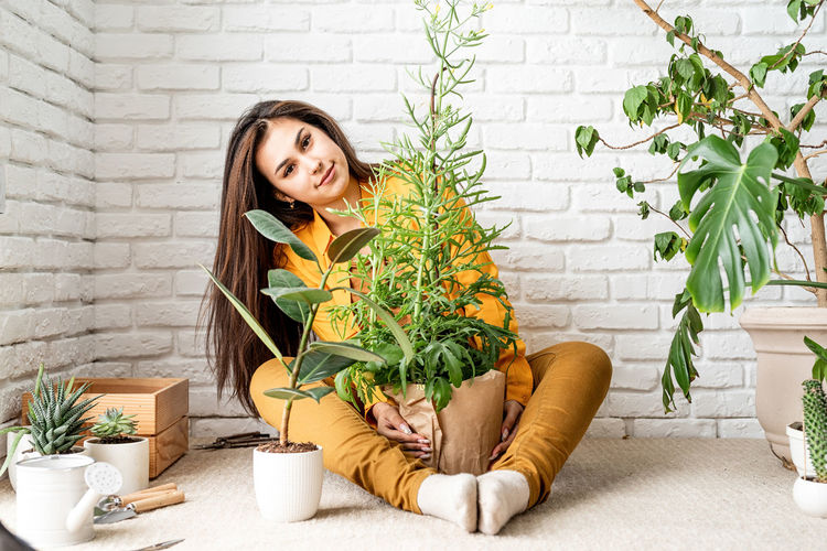 Portrait of smiling woman with potted plants