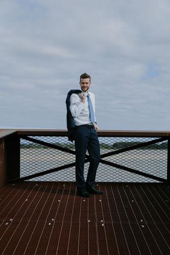 Man standing on bridge against sea