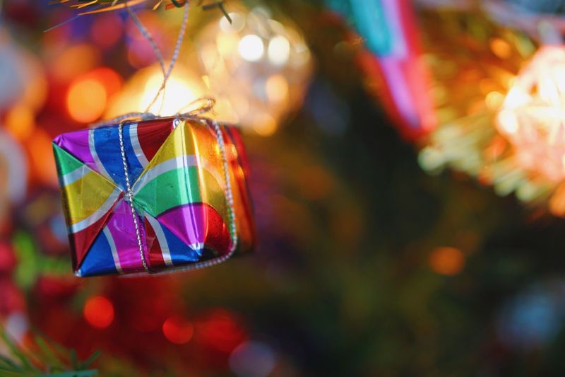 Closed up Christmas ornament hanging on the tree white bokeh lights in background. Festive winter season celebration. New year time. Box Present Xmas Sparkle Ornament Christmas New Year Light Bright Beautiful Festive Bokeh Multi Colored Close-up Hanging Decoration Outdoors Illuminated Reflection Creativity Tree