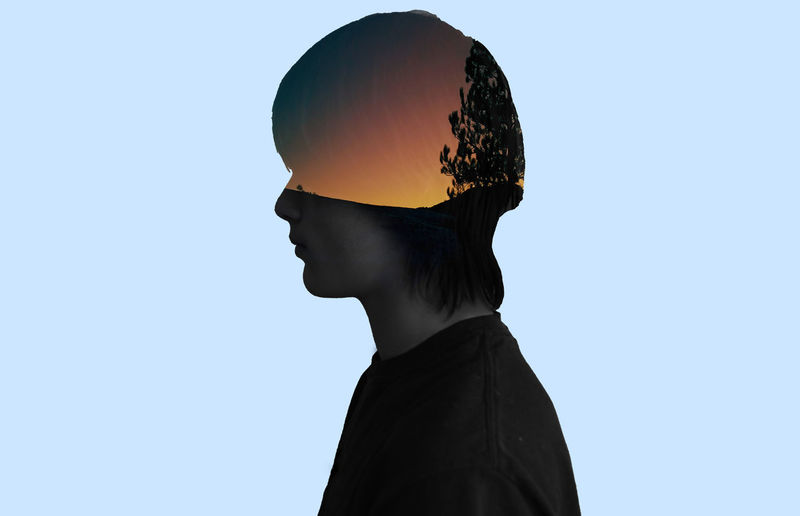 Double exposure tree at sunset and man against blue background