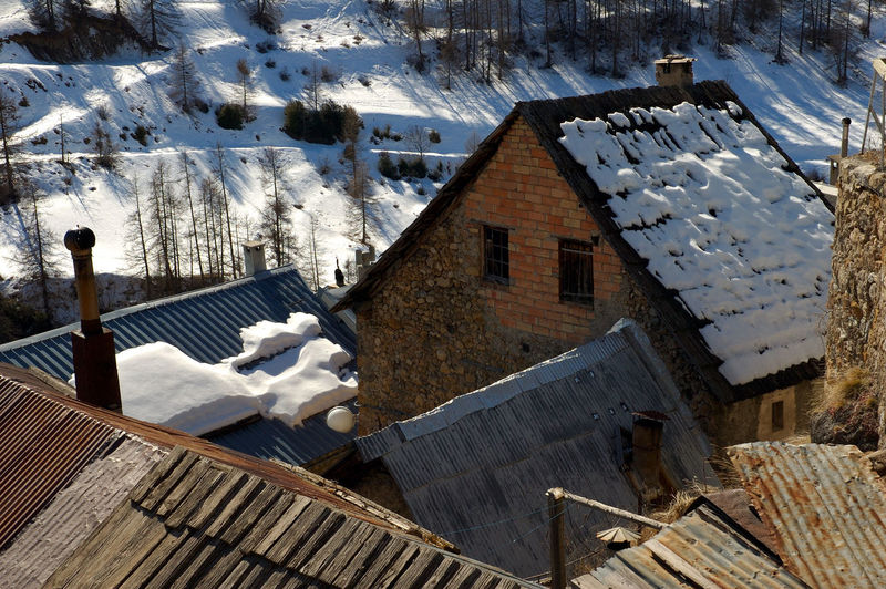 High angle view of houses amidst trees and buildings during winter