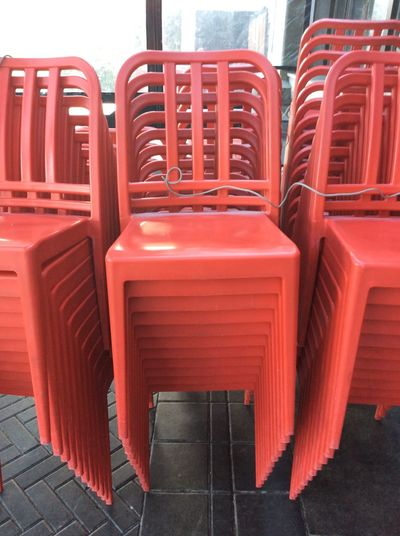 Vancouver Canada Stacked Red Plastic Chairs tied up by steel cable Ordered Neatly Stacked