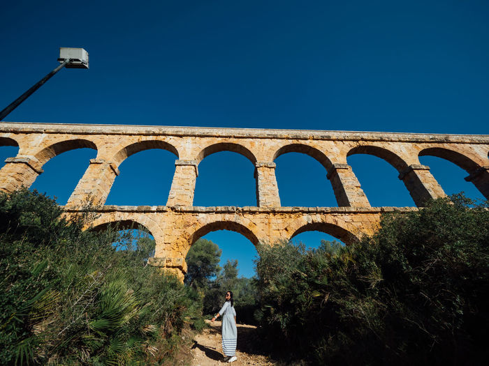 Woman standing against arch bridge