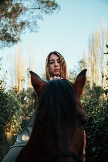 Young woman with horse standing on field against sky