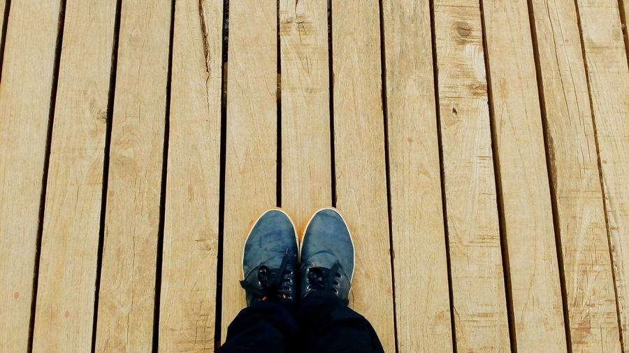 Low Section Of Person Standing On Boardwalk