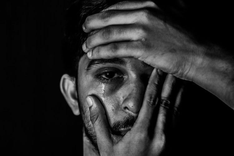 Close-up portrait of man making face over black background