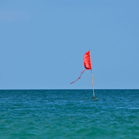 Red flag zone marking in sea near beach Buoy Do Not Cross Far FAR AWAY Flag Horizon Horizon Over Water Limit No Trespassing Ocean Red Flag Red Flag Warning Safe Zone Sea Swim Swimming Warning Warning Sign Zone How Do We Build The World? Blue Wave Summer Exploratorium