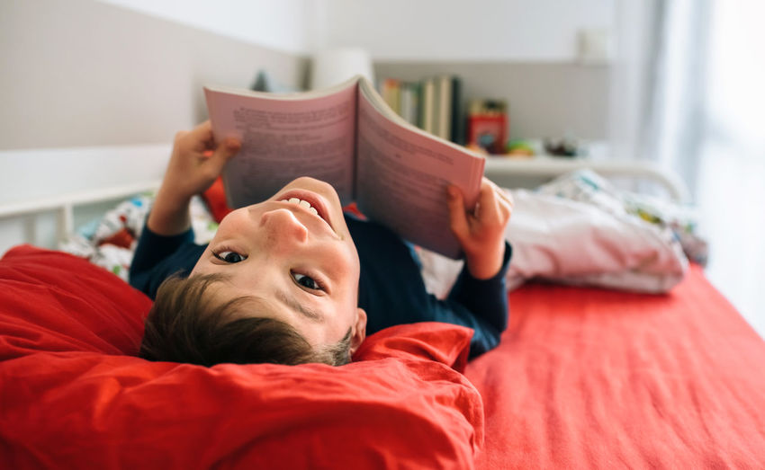 Portrait Of Smiling Boy With Book Lying On Bed At Home