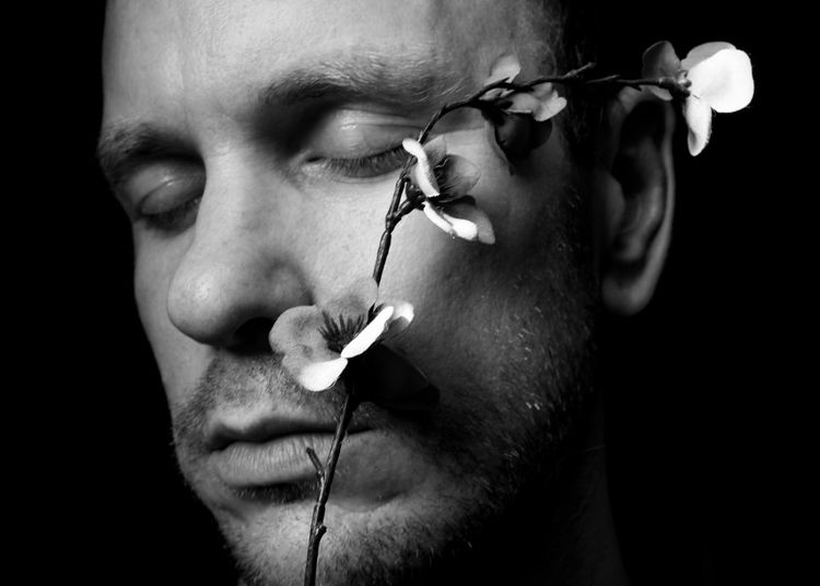 Close-up of man holding flower against black background