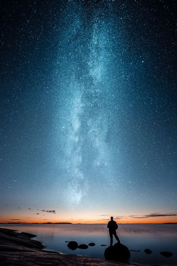 The Milky Way Series for 2018 EyeEm Awards - These are composite images made from 2-3 different shots and blended together in Photoshop by using layers and masks. My inspiration comes mainly from other photographers work that I find in social media especially from another Finnish photographer Mikko Lagerstedt's work. Although I try to have my own touch to my images. I love going out alone by the coast to see the sunset descending below horizon and to do what I love to do most.. photographing and making art. - Silhouette of a man standing on rock by a sea and looking at sunset and stars Jamoimages 2018 EyeEm Awards Star - Space Night Space Astronomy Reflection Silhouette Sky Milky Way People Galaxy Beauty In Nature One Person Star Field Nature Sea Beauty Constellation Scenics The Creative - 2018 EyeEm Awards