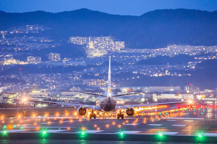 Illuminated airplane on runway against mountains at night