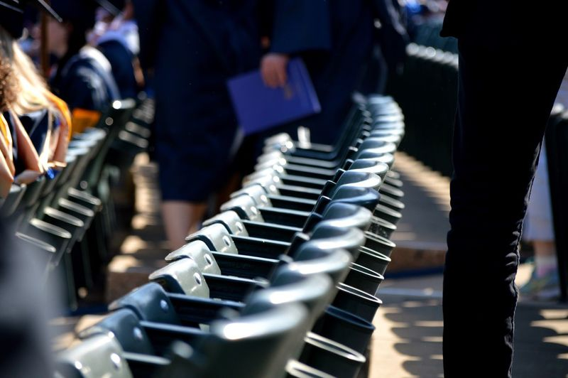 People by seats at webster university during graduation ceremony