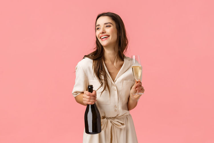 Portrait of a smiling young woman drinking glass against pink background