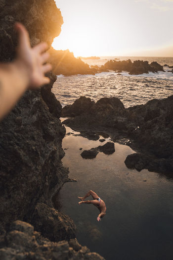 High angle view of man diving in sea against sky during sunset