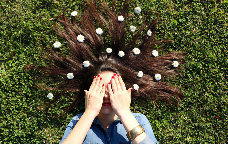 Woman lying on grass covering eyes with flowers in hair