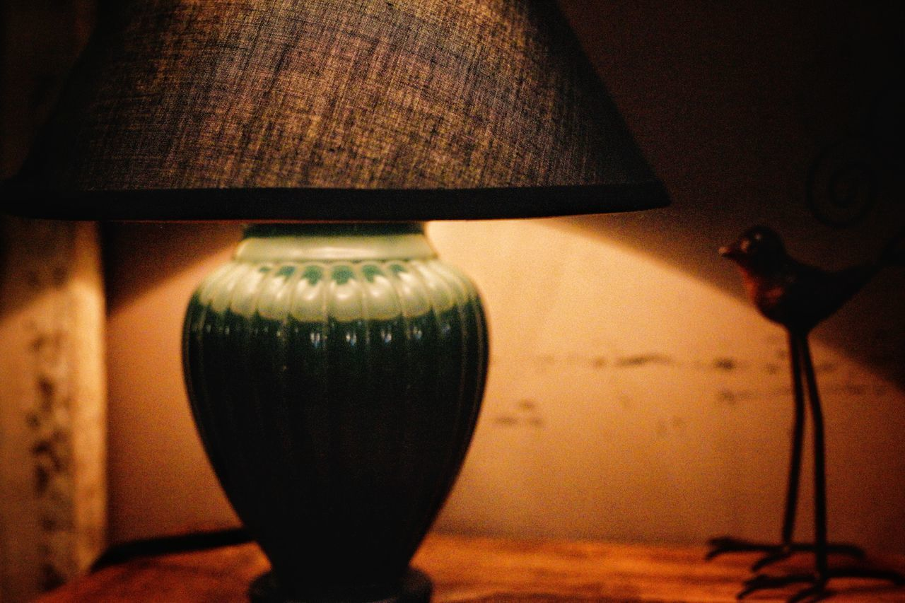 CLOSE-UP OF ILLUMINATED ELECTRIC LAMP ON TABLE