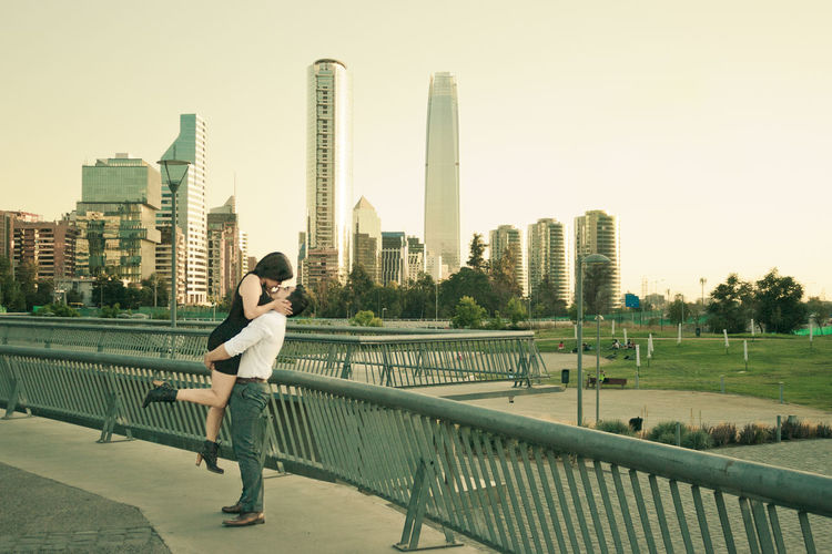 Side View Of Boyfriend Carrying Girlfriend By Railing Against Cityscape
