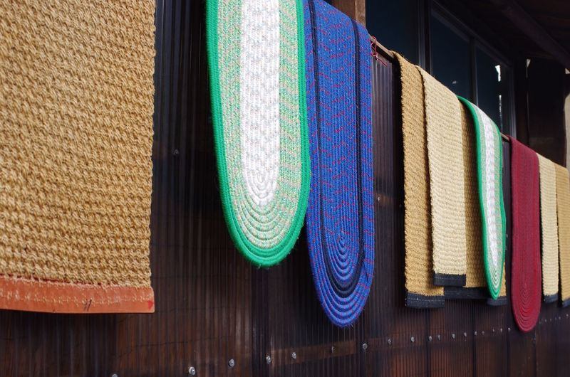 Close-up of doormats hanging for sale at market