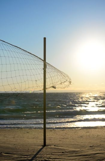 Volleyball net on beach during sunset