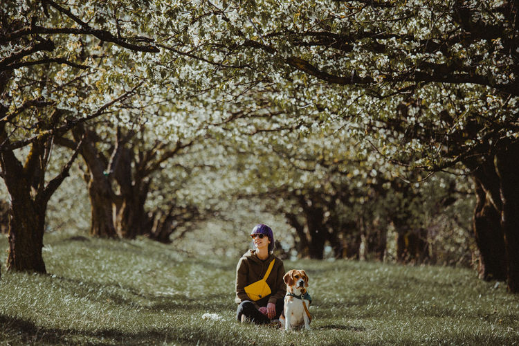 Woman sitting with dog on land at park
