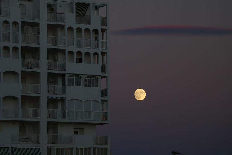 Building in the night against bright moon Moon Architecture Built Structure Building Exterior Night Building Sky No People Full Moon City Outdoors Dusk Geometric Shape Circle Nature Illuminated Residential District Shape Space Dark Planetary Moon Moonlight