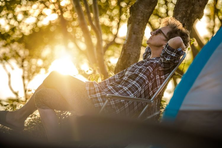 Side view of woman sitting on chair against trees during sunset