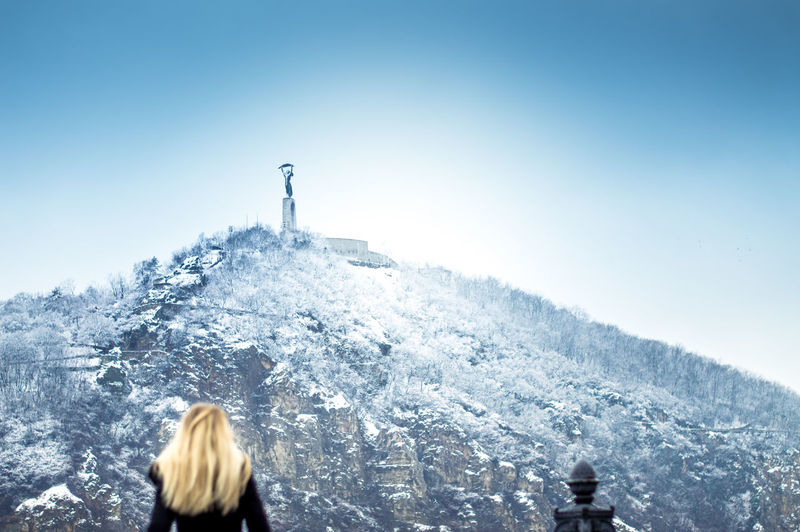 Woman standing on snow covered mountain against clear sky