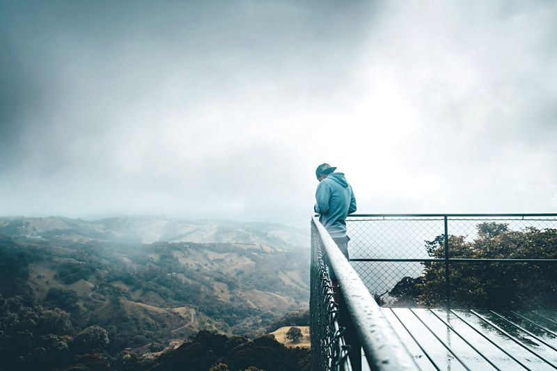 Man Standing At Observation Point By Landscape Against Cloudy Sky