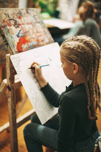 Beautiful teenage girl with pigtails at art school draws graphics with pen on easel,