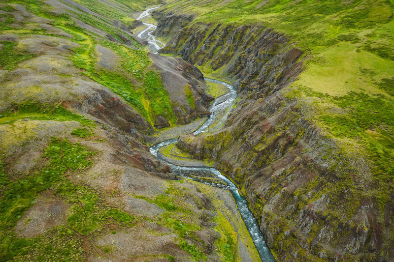 Drone view over green hills, canyon and small river in iceland, summertime.