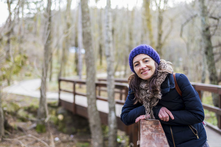 Front view portrait of beautiful girl with backpack standing near old footbridge. She is having break during hike in coniferous forest Winter Warm Clothing Looking At Camera Cold Temperature Clothing One Person Portrait Tree Young Women Leisure Activity Young Adult Real People Hat Knit Hat Women Front View Lifestyles Smiling Day Outdoors Beautiful Woman Scarf Standing Woman Females Traveler Backpack Backpacker Hat Exploration Adventure Mountain Forest Hiker Nature