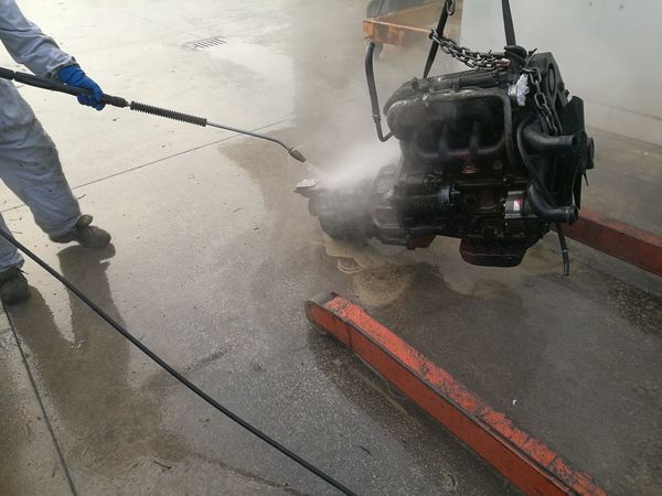 Technical pressure washer cleans engine Check Clean Cleaner Engine Engineering Inspection One Person Pressure Washer Repair Service Spray Station Suspended